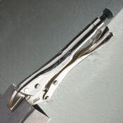 A straight jaw locking pliers acting as a vise grip by clamping two pieces of sheet metal together