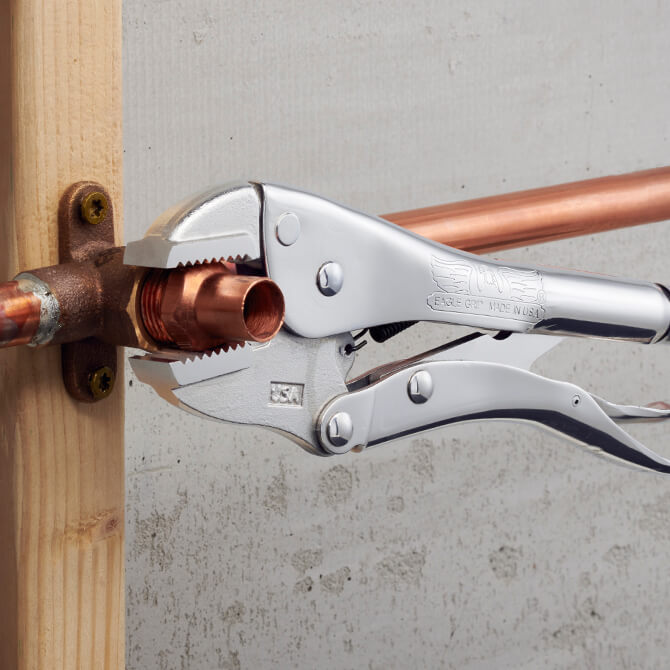 10 Inch long Eagle Grip Locking Pliers with straight jaws clamping to a piece of copper pipe