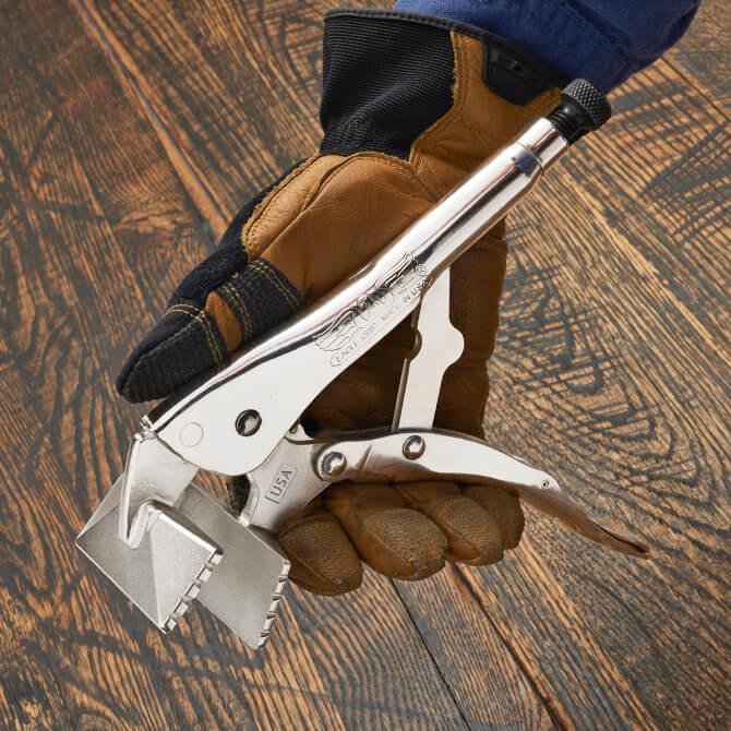 La mano de una persona abre unas pinzas Eagle Grip para lámina de metal