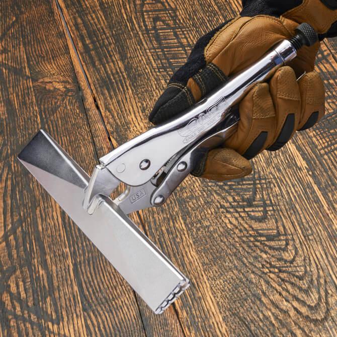 Una mano con guante sostiene unas pinzas Eagle Grip para lámina de metal