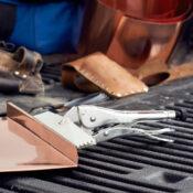 Un sellador de presión Eagle Grip de 9 pulgadas doblando una pieza de cobre en la parte posterior de la caja de una camioneta