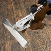 Mano con guante abriendo unas pinzas Eagle Grip para lámina de metal