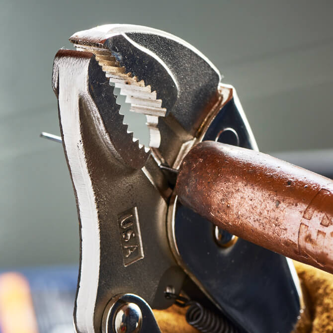 A curved jaw locking pliers being used to cut a piece of welding wire