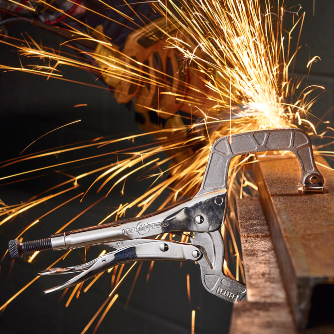 An Eagle Grip Locking C Clamp with swivel pads creating a vise on a piece of bar stock while a welder uses a grinder in the background creating sparks