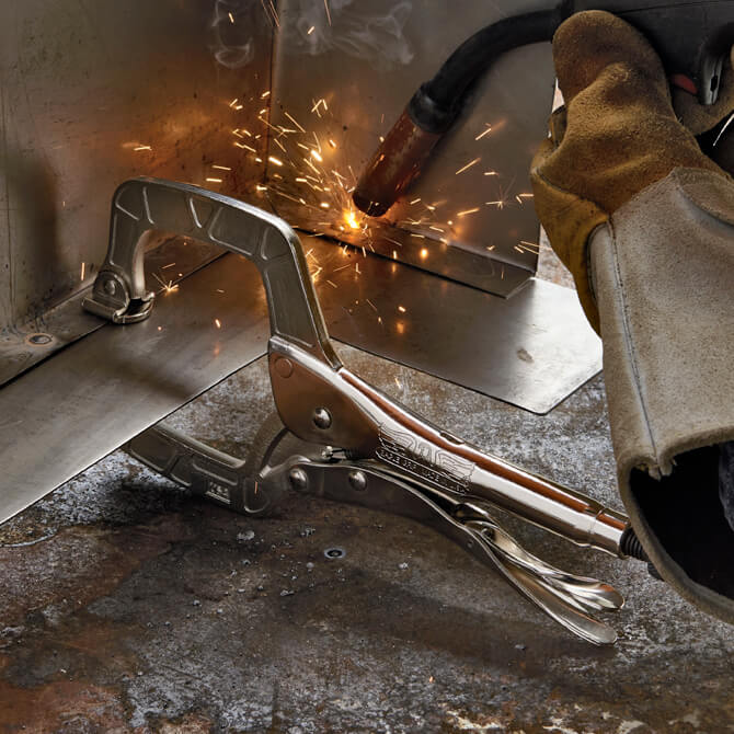 An Eagle Grip Locking C Clamp vising its swivel pad tips on two pieces of sheet metal while a welder uses a torch to weld the metal together