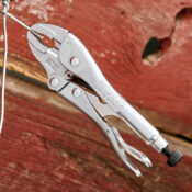 A 7 Inch Curved Jaw Locking Pliers clamping on to a piece of farming wire